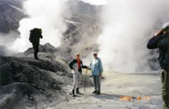 Hikers near steaming volcanic activity.